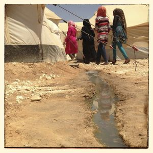Samar*, Hiba*, Jana* and Rahma* walk past a waste water stream