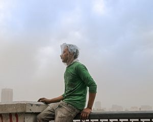 A boy along the Corniche al-Nil uses a shopping bag to protect himself from tear gas. © Domenico D'Alessandro