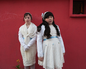 Ilona, 12 years olds, and her sister , Maddelena 11 years old, standing in front of a wall of their neighbourhood, the Cité Gély, in Montpellier, before going to Saint Cléophas church for their first communion.