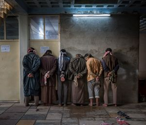 """""""Iraqi men from the Hawija region of Iraq wait to be questioned by Kurdish security personnel at a base near Kirkuk. Having fled areas still under the control of ISIS militants, men and boys of fighting age are vetted for any links to the group before being allowed to join their families in camps for displaced people in the Kurdish-controlled region of the country""""."""