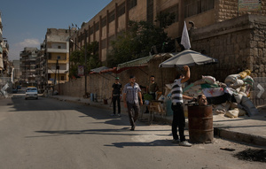 Aleppo, Syria: FSA (Free Syrian Army) fighters amuse themselves with a bust of Assad at the entrance to Salaheddin.