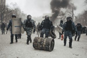 Riot police barrel the roll and carry tires, which they took away from protesters during the attack in the center of Kiev on Jan. 22, 2014.