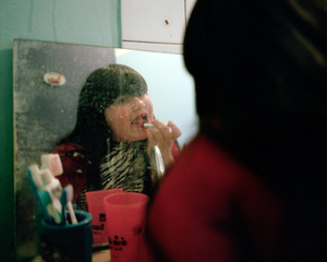 Maddelena putting a vivid red liptstick on her lips, in the bathroom, before going out to play in the streets of her neighbourhood.