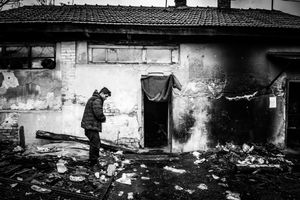 Man at the front of abandoned building, which is his temporary shelter, at the back the main train station. Belgrade, Serbia.