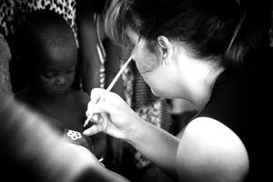 Volunteer of the NGO painting the hands of children during medical care in a village supported by the project.