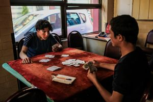 A small cafe in Küçük Pazar, an area which is full of Syrians day and night. The young people spend their time smoking, gossiping and playing cards.  Many of the people who have money to gamble get it by sending their younger siblings out on the street to beg. © Turjoy Chowdhury