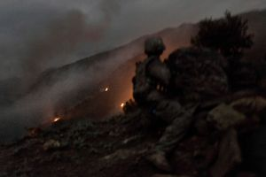 A U.S. soldier from the 1st Infantry Division takes cover while watching the hillsides of Loi Kolay Village being mortared and bombed by U.S. forces in the Korengal Valley, Afghanistan, on April 7, 2009. Two squads came under attack as they left Loi Kolay Village while on a patrol to question village elders. © Adam Ferguson