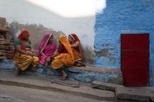 A group of women chatting and relaxing outside one of their houses