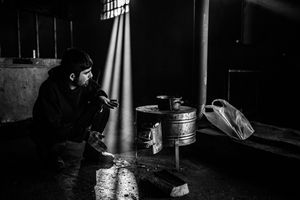 Man makes tea on the makeshift stove and tries to warm himself inside a derelict warehouse in Belgrad, Serbia.