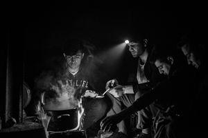 Migrants cooking food on the fire. Inside derelict warehouse in Belgrade, Serbia.