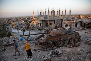 Kurdish couple walks by a destroyed tank in the rubble in the destroyed town of Kobane, Syria, on 18 April, 2015.
