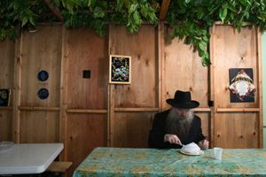 Rabbi Herschel Gluck eating a takeaway meal in his Sukkah during the festival of Sukkot, the feast of Tabernacles. The holiday commemorates the forty-year period during which the children of Israel were wandering in the desert. In honor of the children of Israel in the wilderness, men dwell in temporary shelters.