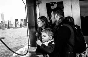 Passengers onboard the Staten Island Ferry look across the New York Harbor at the Financial District.