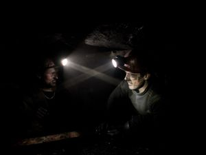 Two miners lying down while working. Working conditions are difficult and the risk of accidents is very high.