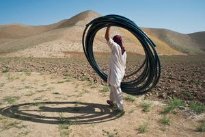 © Iva Zimova. A man carries a bundle of plastic hose that will be used to irrigate a pistachio orchard.