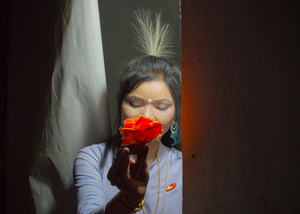 During the Lai Haraoba festival of Manipur a Maibi priestess poses for the camera holding a paper flower.