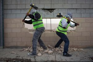 Palestinian activists brake parts of the Wall, during a direct action against the Separation Wall and the occupation, West Bank, 2013.