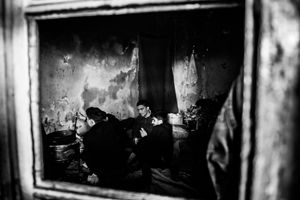 """Man during cooking. View through a window into one of the """"rooms"""" in abandoned warehouse in Belgrad, Serbia."""
