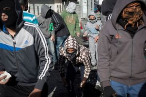 Palestinian youth throw stones, during clashes with Israeli border police at a checkpoint between Shuafat refugee camp and Jerusalem, November 7, 2014. Clashes broke after a Palestinian man drove a car into a crowd, killing a policeman and injuring 13 people in Jerusalem on November 5th.