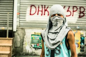 A far left-wing protester of PKK youth organisation YDG-H behind barricades during clashes with riot police at anti-government demonstration in Istanbul's Gazi neighborhood, Turkey.
