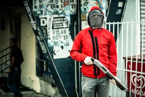 A far left-wing protester of PKK youth organisation YDG-H armed with a shotgun during clashes with riot police at anti-government demonstration in Istanbul's Gazi neighborhood, Turkey.