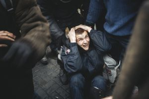 Police man covers the head from the blows of protesters, after being beaten by protesters during a clash between protesters and police. Kiev, Feb. 20, 2014