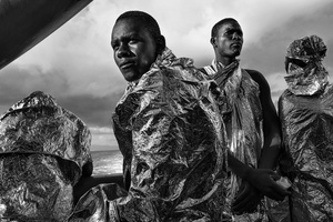 Migrants wrapped in emergency blankets two days after being rescued catchsight of the Italian coast for the first time; Strait of Sicily, Mediterranean Sea, 23August 2015.