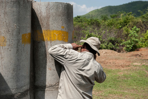 Golden West Humanitarian Foundation employee blocks his ears and watches as recovered UXO is disposed of, Golden West developed a UXO harvesting programme where they recycle UXO into shaped charges which are then used to destroy other pieces of UXO in the field.