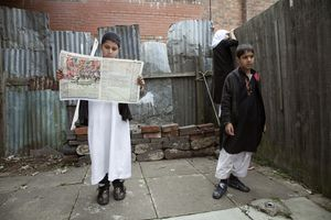 Backyard A group of Muslim children in the backyard of their terraced house. Their formal Islamic dress is only worn for their daily afterschool mosque class. The eldest boy checks the football results in the local paper; his sister speaks with their neighbour, a Jehovahs Witness, over the fence.   © Liz Hingley
