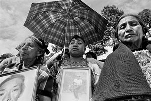 Widows and children of the disappeared hold photos of the men they search for at a demonstration at Comalapa on the Day of the Dead. The crowds that attend the exhumation daily are overwhelmingly female, searching for their male relatives that disappeared during the war. © Victor Blue, 2004