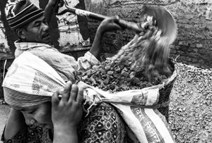 A woman carrying a basket of rocks and material for rebuilding homes destroyed by the earthquake.