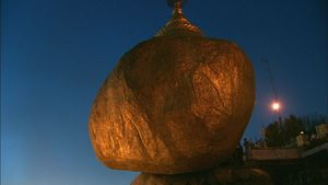 GOLDEN BOULDER FROM BELOW <BR>At the peak of Mount Kyaikhtyo in Eastern Burma (Myanmar) a precariously-balanced golden boulder draws worshippers to witness the alignment of the full moon. Atop the boulder is a pagoda inside which is a single hair from the head of the Buddha, thought to keep the boulder from falling over the cliff below. © Peter Friedman and © Roger Manley