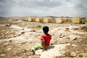 Bedouin boy watching the building of the Carmel settlement on land that his community claims ownership over. South Hebron Hills. April 2010 © Lars Håberg