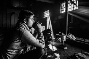 Refugees make tea on makeshift stove inside a derelict warehouse in Belgrade. Serbia.