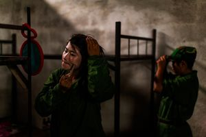After finishing morning training a young woman applies thanaka to her face inside the women's room at the military base outside of Laiza, Kachin State, Myanmar, May 17, 2013. The 9 women shared an unlit room throughout the two-month training.     © Adriane Ohanesian