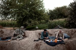 Afghan National Police broke their fast for Iftar during Ramadan while a soldier from the 504th U.S. Military Police Battalion provided security in the Mehlajat area of Kandahar City, Afghanistan on September 6, 2010. © Adam Ferguson
