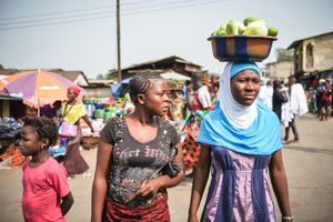 Women wait to cross a road after visiting the market.