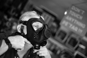 """Dallas, Texas, 2010. Harold Rosenbaum demonstrates the gas mask that he keeps by his bed, to aid escape from a burning house or tear gas. """"When I was a parachuter in the 82nd Airborne Division, I once lived in one of these for 72 hours"""" he said. © Spike Johnson"""