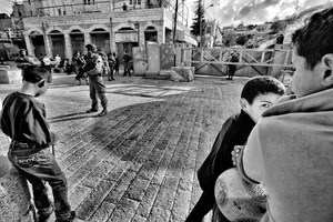 Palestinian children linger in front of the Israeli military guarded Beit Romano settlement in Hebron. Apr. 4, 2011. West Bank, Palestine.