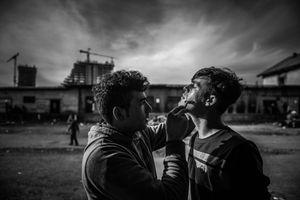 Men during shaving In temporary shelter behind main train station  in Belgrade, Serbia.