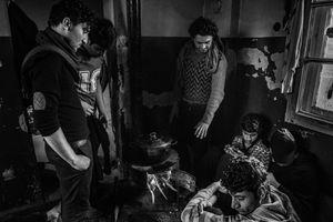 Inside abandoned building, migrants prepare meal together. Belgrade, Serbia.