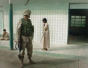 Baghdad, Iraq (2003). A US marine secures the Al Rashad psychiatric hospital, women ward.