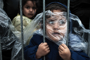 A child is covered with a raincoat while she waits in line to register at a refugee camp in Preševo, Serbia, 07 October 2015
