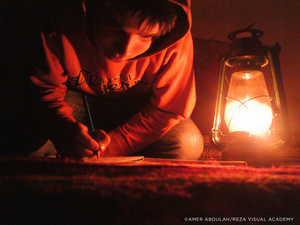 Within the privacy of his tent, a child does his homework after darkness falls over the camp.