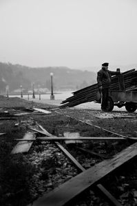 Collecting spare material from abandoned warehouses on the harbor in Aigion under the rain