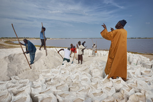 A buyer gives the workers instructions for packing the salt.
