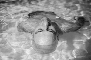 Weak from chemotherapy, Howie Borowick floats effortlessly and slowly around the pool during a midweek getaway to a warm climate. Naples, Florida. January, 2013 © Nancy Borowick