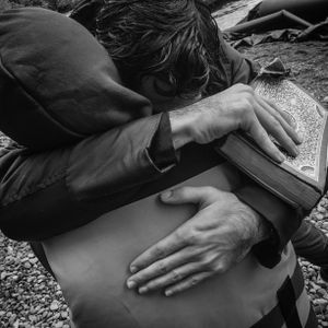 Refugees embrace after landing by boat in Lesbos, Greece.