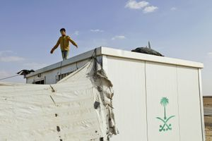 A boy standing on the roof of his container home, trying to capture a pigeon. © Tom Verbruggen