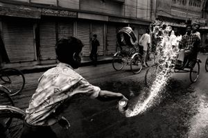 Shop assistant settling the dust in early morning. Bongshal, 2006. © Munem Wasif